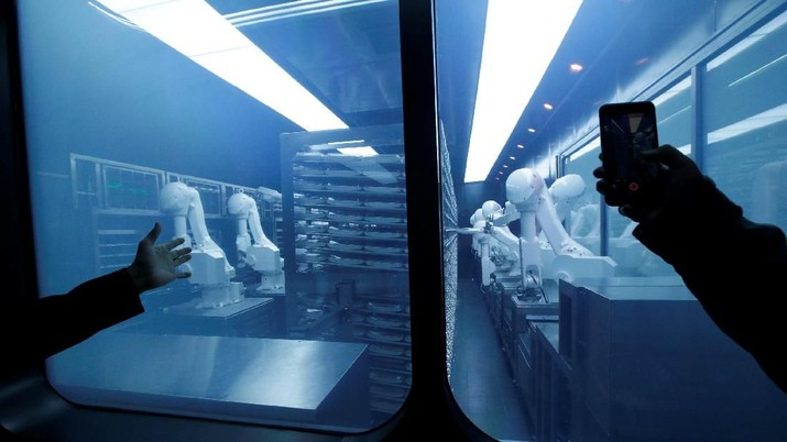 A customer takes a picture as robotic arms collect pre-packaged dishes from a cold storage, done according to the diners' orders, at Haidilao's new artificial intelligence hotpot restaurant in Beijing, China, November 14, 2018. Picture taken November 14, 2018. REUTERS/Jason Lee