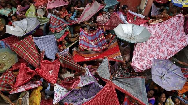 Umat Hindu menengadahkan pakaian dan payung untuk menampung beras dari sebuah kuil di Festival Annakut, Kolkata, India. (Reuters/Rupak De Chowdhuri)