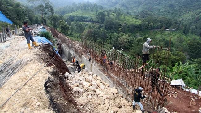 Sejumlah pekerja menyelesaikan pembangunan dinding beton penahan longsor di jalur Puncak, Bogor, Jawa Barat, Selasa (13/11). (ANTARA FOTO/Yulius Satria Wijaya)