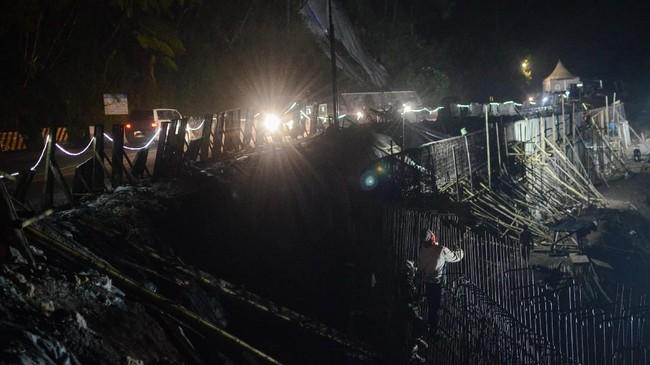 Pekerja memasang rangka beton pada proyek pembangunan dinding penahan longsor di Jalan Raya Puncak, Kabupaten Bogor, Jawa Barat, Jumat (26/10). (ANTARA FOTO/Raisan Al Farisi)