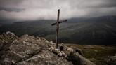 Salib sederhana yang terbuat dari kayu, ditancapkan di antara bebatuan dan tengkorak kepala domba, diambil pada 20 Agustus 2018. (Photo by JEFF PACHOUD / AFP)