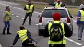 Di wilayah timur Savoie, Prancis, seorang ibu panik karena mobilnya terkepung para pengunjuk rasa saat hendak membawa putrinya ke dokter. Seorang wanita berusia 63 tahun pun tewas tertabrak mobil. Pengemudi, yang disebut polisi dalam keadaan syok, sudah dibawa untuk dimintai keterangannya. (REUTERS/Stephane Mahe)