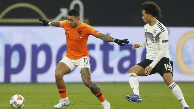 Gelandang serang timnas Belanda Memphis Depay berduel dengan Leroy Sane. Skor 2-0 untuk tuan rumah bertahan hingga akhir babak pertama. (REUTERS/Leon Kuegeler)