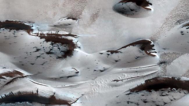 Bukit pasir paling utara di Mars bernama Marsimenampakan usainya musim dingin dengan es karbondioksida. Bintik gelap adalah tempat di mana es retak dan awal musim semi, melepaskan pasir. (REUTERS/NASA)