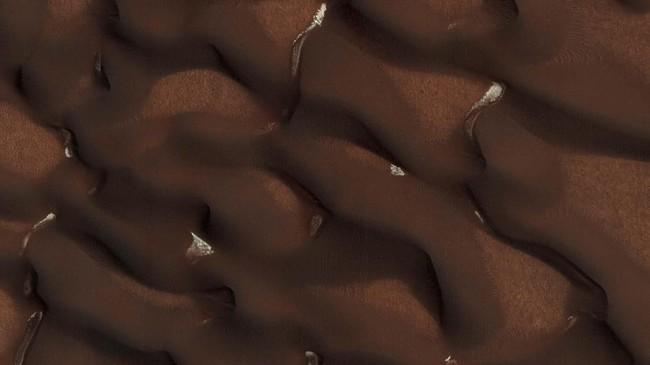 Gundukan pasir di Marsyang mulai terlepas dari lapisan es musiman selama awal musim panas Mars, dengan kantong es masih terlihat di area yang terlindungi. (NASA via REUTERS)