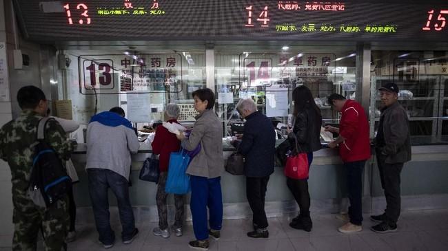 Tengok saja warga yang mengantre di Rumah Sakit Yueyang, Shanghai, China. Mereka mengantre untuk mendapatkan obat-obatan herbal. (Photo by Johannes EISELE/AFP)