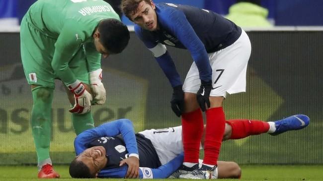 Antoine Griezmann berusaha membantu rekan setimnya, Kylian Mbappe, yang mengalami cedera bahu. Mbappe akhirnya ditarik ke luar dan digantikan dengan Florian Thauvin pada menit ke-36. (REUTERS/Charles Platiau)