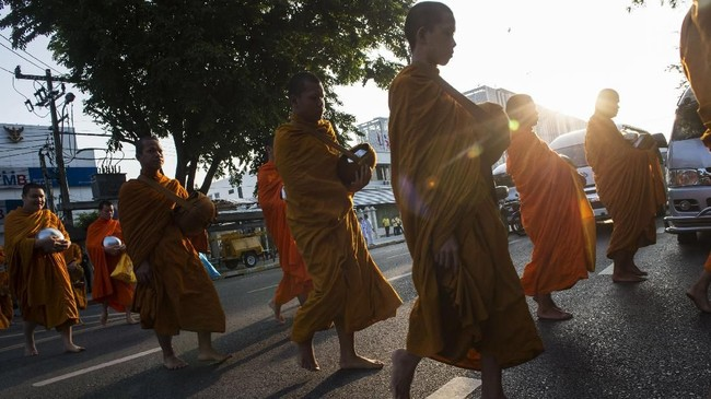 Kalangan biksu di Thailand tengah berjuang melawan krisis obesitas. Setiap pagi, mereka berjalan-jalan dan berolahraga ringan di sekitar kuil demi menurunkan berat badan.(Photo by Romeo GACAD/AFP)