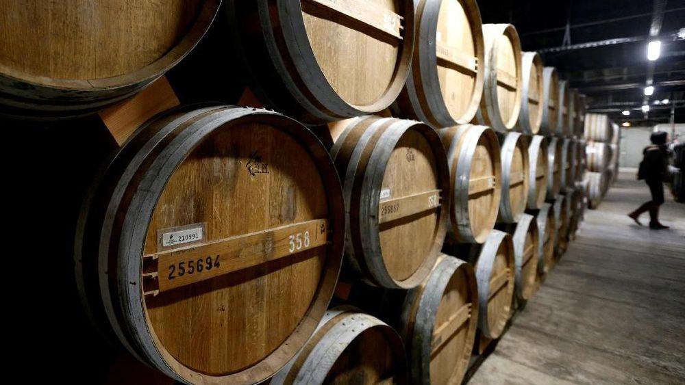 Pekerja melintas diantara barel yang di simpan di ruang bawah tanah untuk menyimpan Cognac lanka dan tua di pabrik Remy Martin, Perancis. (REUTERS / Regis Duvignau)
