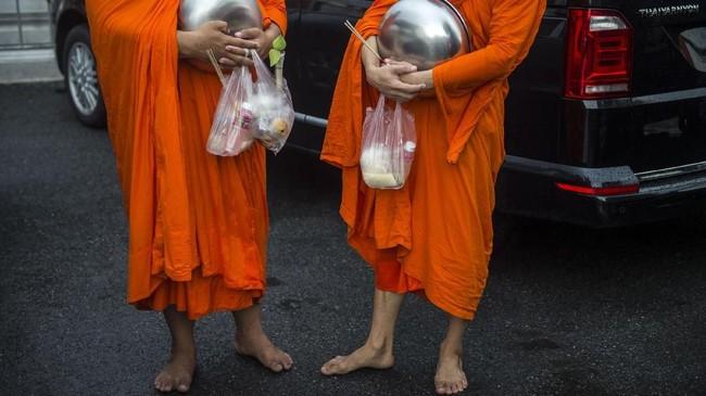 Obesitas memang tengah melanda para biksu di Thailand. Penyebabnya adalah sajian makanan pemberian umat. Tingginya kandungan gula dan lemak dalam makanan-makanan itu berkontribusi menimbulkan krisis obesitas para biksu. (Photo by Romeo GACAD/AFP)