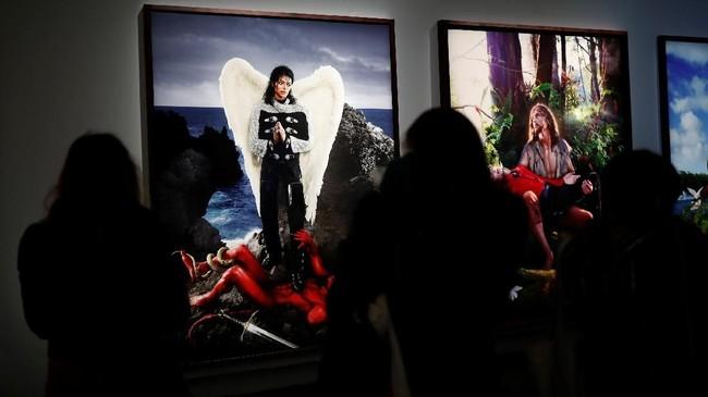 Pengunjung terlihat berkerumun di depan karya seni yang dikerjakan oleh David LaChapelle, yang memberi sentuhan sayap di punggung Michael Jackson. (REUTERS/Benoit Tessier)