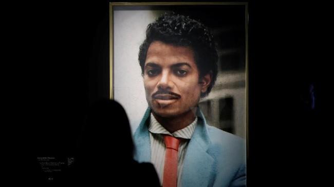 Artis Hank Willis Thomas menampilkan Michael Jackson sewaktu belum banyak terkena pisau bedah di meja operasi, dalam tajuk 'Time Can Be a Villain or a Friend'. Sepanjang kariernya, penampilan Jackson selalu dibicarakan publik. (REUTERS/Benoit Tessier)