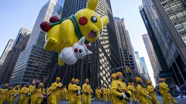 Balon karakter animasi Jepang, Pikachu, ikut diterbangkan dan diarak bersama penari dengan kostum serupa. (AFP PHOTO/Don Emmert)