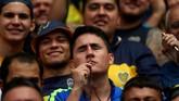 Salah satu fan Boca Juniors mencium kalung rosario demi keberuntungan timnya saat leg pertama final Copa Libertadores. Masih banyak fan dari kedua tim yang percaya hal-hal mistis di sepak bola. (REUTERS/Marcos Brindicci)