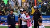 Striker Boca Juniors Carlos Tevez meladeni salah satu fan yang masuk lapangan dan memeluknya pada sesi latihan jelang bertandang ke markas River Plate. (REUTERS/Marcos Brindicci)