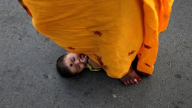 Seorang perempuan pemeluk agama hindu melangkahi seorang anak untuk meminta anugerah Dewa Matahari untuk sang anak. Ritual ini dilakukan saat perayaan keagaam Chhath Puja di Kolkata, India. (REUTERS/Rupak De Chowdhuri)