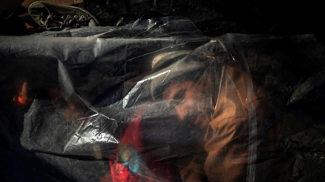Seorang pria pengungsi --bagian dari ribuan orang yang coba masuk ke Amerika Serikat dari Amerika Tengah--terbangun di bawah suatu terpal yang menaungi keluarganya. Ia berada di penampungan pengungsi di Tijuana, Meksiko. (REUTERS/Adrees Latif)
