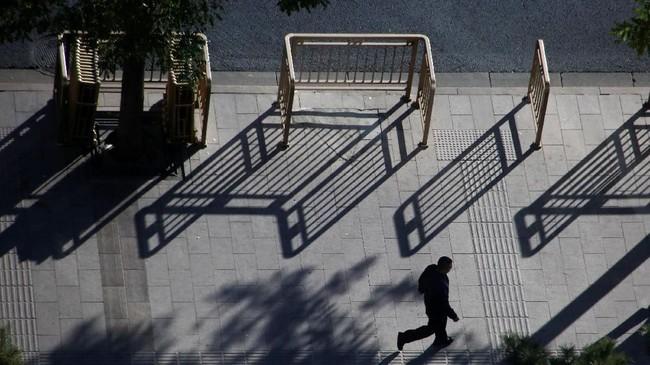 Seorang pria berjalan di Chang'an, Beijing, sementara di sekitarnya terlihat bayangan-bayangan panjang pembatas jalan. (REUTERS/Thomas Peter)