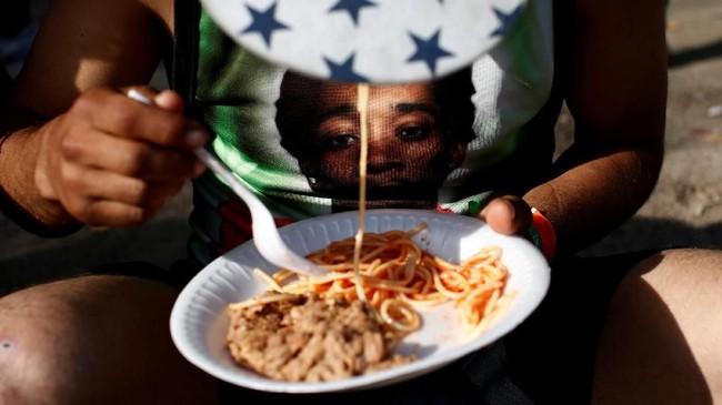 Seorang imigran dari Honduras --bagian dari ribuan orang yang coba masuk ke Amerika Serikat dari Amerika Tengah-- memakan makanan yang ia terima di penampungan di Tijuana, Meksiko. (REUTERS/Kim Kyung-Hoon)