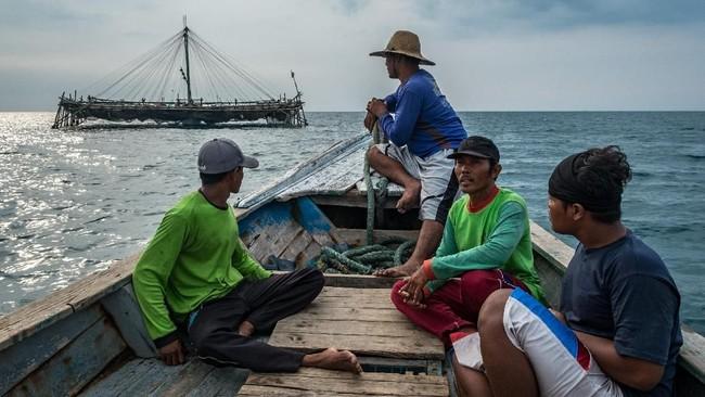 Musafa (tengah) bersama sejumlah buruh nelayan menuju bagan apung miliknya di perairan Demak, Jawa Tengah. (ANTARA FOTO/Aji Styawan)
