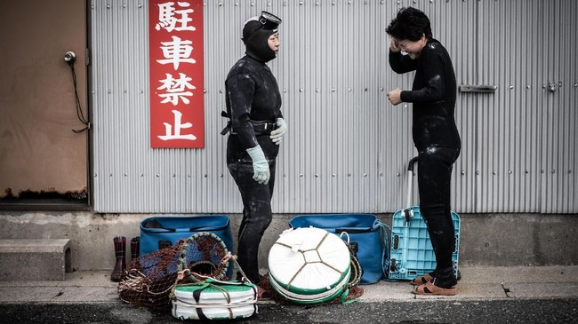 Sekelompok nenek-nenek Jepang muncul dari sebuah perahu yang kembali ke pantai. Dibalut pakaian selam hitam, mereka adalah bagian dari komunitas nelayan