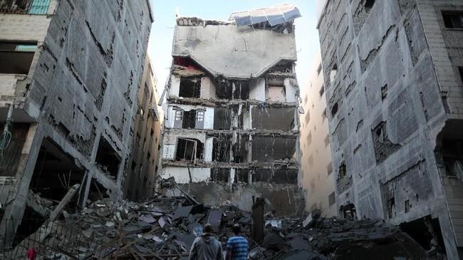 Warga Palestina berdiri di dekat sisa-sisa bangunan yang hancur oleh serangan udara Israel, di Kota Gaza (REUTERS/Suhaib Salem)