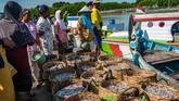 Pedagang antre untuk membeli hasil tangkapan ikan teri dari nelayan bagan apung di Pelabuhan Perikanan Pantai Morodemak, Bonang, Demak, Jawa Tengah. (ANTARA FOTO/Aji Styawan)