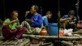 Musafa (kedua kiri) menyantap makan malam bersama buruh nelayan di atas bagan apung di perairan Demak, Jawa Tengah. (ANTARA FOTO/Aji Styawan)