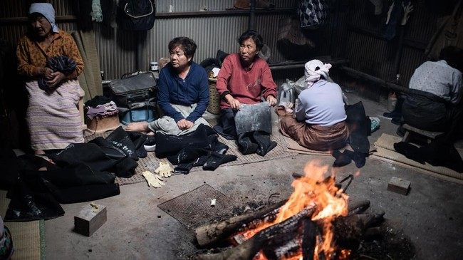 Para Ama berkumpul di dekat perapian setelah selesai melaut. (Martin BUREAU / AFP)