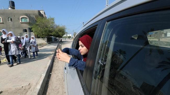 Wanita Palestina Fatma Abu Musabbeh menggunakan ponselnya untuk mengambil gambar saat dia melihat keluar dari jendela mobil di Jalur Gaza tengah. (REUTERS/Mohammed Salem)