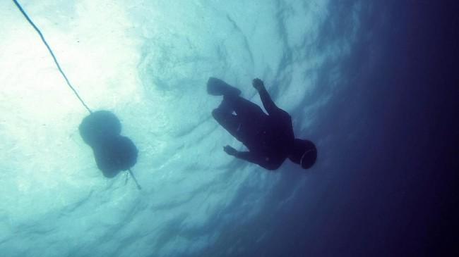 Para wanita yang berusia antara 60 hingga 80 tahun dapat disalahartikan sebagai remaja di bawah air, meluncur dengan anggun di kedalaman laut Pasifik yang gelap. (Martin BUREAU / AFP)
