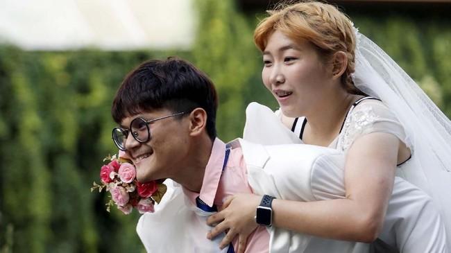Mereka harus berlari untuk menemui pengantin pria. Pengantin pria pun harus menggendong pengantinnya untuk menyelesaikan pertandingan. (REUTERS/Soe Zeya Tun)