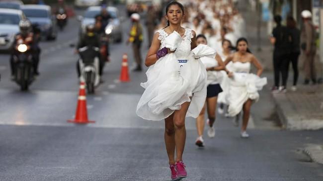 Namun berbeda dari kompetisi lari biasa, mereka harus memakai gaun pengantin saat berlari di jalanan. (REUTERS/Soe Zeya Tun)