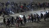 Para petugas pun menembakkan gas air mata hingga imigran di dekat perbatasan itu membubarkan diri, sementara helikopter aparat Meksiko berputar di atas mereka. (Reuters/Hannah McKay)