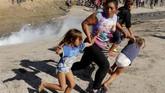 Mereka pun tetap memaksa masuk. Pada Minggu (25/11) pagi, mereka sudah berkumpul di jembatan di Meksiko menuju AS. (Reuters/Kim Kyung-Hoon)