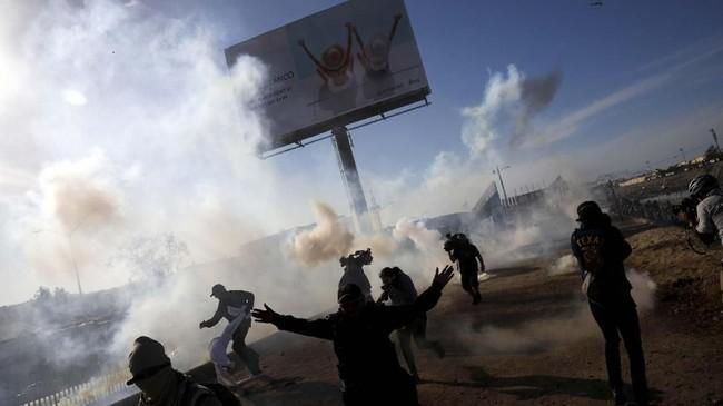 Menempuh perjalanan panjang demi menghindari baku tembak antar-geng di kampung halamannya, para imigran dari Honduras masih harus menghadapi tembakan gas air mata ketika mereka mencoba menerobos perbatasan Meksiko menuju Amerika Serikat. (Reuters/Alkis Konstantinidis)