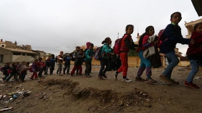 Mereka terpaksa belajar di sekolah dengan kondisi seadanya lantaran rusak akibat pertempuran. (REUTERS/Aboud Hamam)
