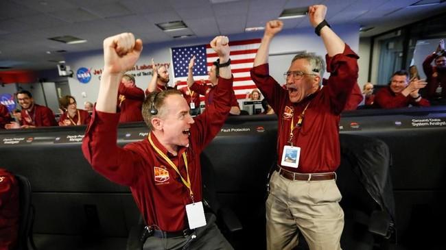 Insinyur NASA, Kris Bruvold dan Sandy Krasnermenunjukkan kelegaannya saatpesawat ruang angkasa InSight mendarat di permukaan Mars setelah enam bulan perjalanan. (Al Seib/REUTERS)