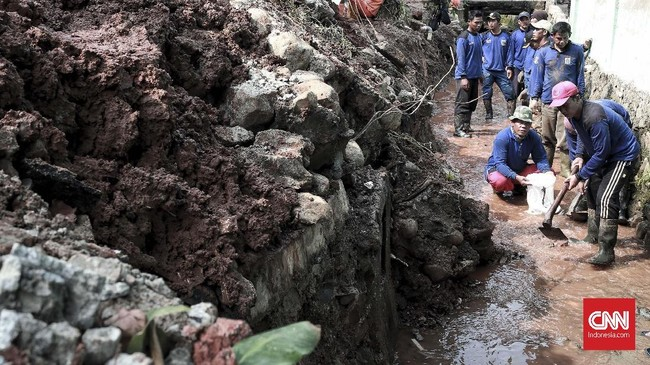 Longsor itu dikatakan bermula dari sebuah lubang dengan besar hampir satu meter di jalan kompleks tepat di depan rumah yang rusak. Pemilik rumah dengan nomor 278 itu mengatakan lubang itu membesarpada minggu (25/11) siang akibat ban mobil warga yang terjebak di sana. (CNN Indonesia/Andry Novelino)