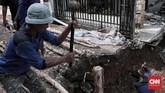 Petugas dari Dinas Sumber Daya Air atau lebih dikenal dengan sebutan pasukan biru mematok tiang pancang agar tak terjadi longsor susulan, Selasa (27/11). (CNN Indonesia/Andry Novelino)