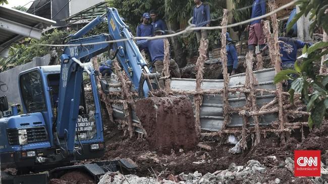 Alat berat yakni eksavator diterjunkan untuk membersihkan tanah dan puing bangunan pascaperistiwa longsor di Kalisari, Pasar Rebo, Jaktim. (CNN Indonesia/Andry Novelino)