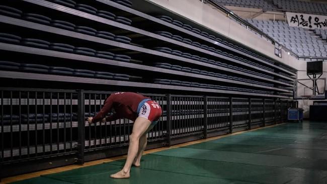 Dalam pertandingan gulat ini, kekuatan dan tehnik adalah kuncinya. Seorang pegulat terlihat sedang melakukan peregangan. (Photo by Ed JONES / AFP)