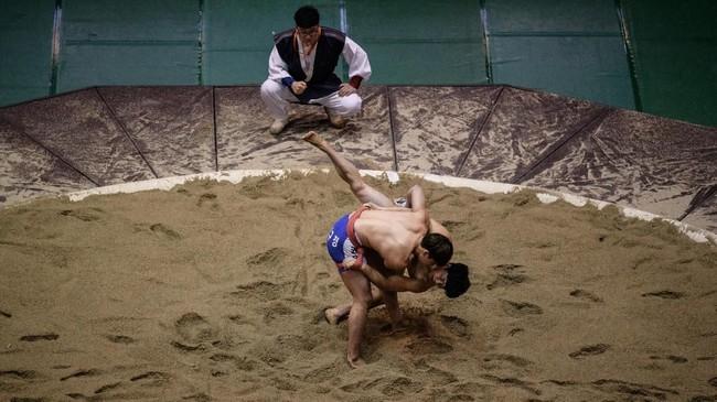 Ssrieum adalah salah satu olahraga tertua yang masih bertahan di Korea sampai saat ini. (Photo by Ed JONES / AFP)
