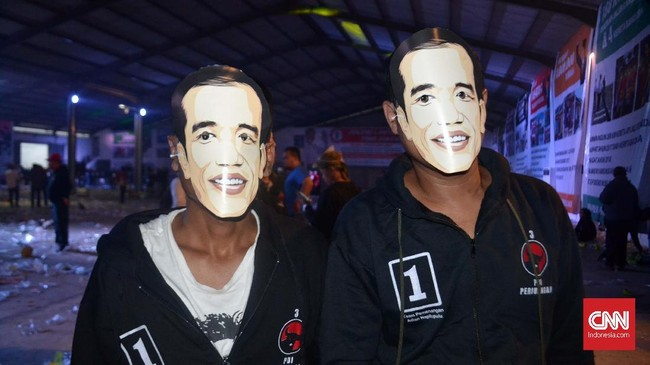 Latar belakang para relawan yang hadir menggunakan topeng Jokowi itu karena tema kegiatan deklarasi dan pelantikan tim kemenangan itu adalah Jokowi Lantik 7.000 Jokowi.(CNN Indonesia/ Harvey Darian)