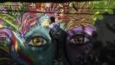 Seorang artis mural mengerjakan gambar mata memandang untuk San Carlos yang lebih baik. (Photo by JOAQUIN SARMIENTO / AFP)