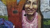 Dulunya, San Carlos dikenal sebagai kota yang penuh kekerasan. Seperti sebuah harapan baru, seorang bayi tengah bermain di depan salah satu mural. (Photo by JOAQUIN SARMIENTO / AFP)