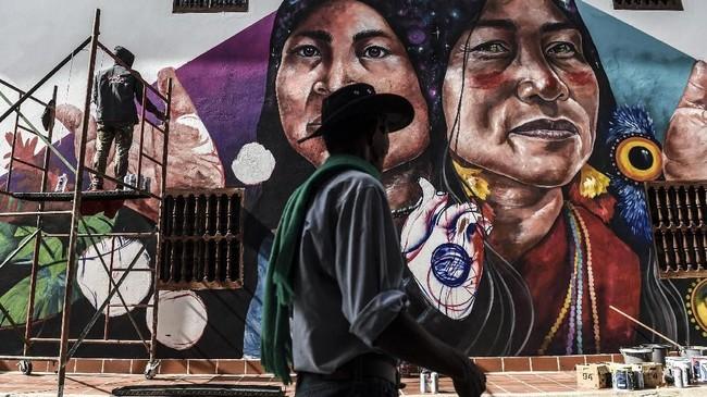 Warga yang melintas menyempatkan diri memperhatikan seorang artis mural yang sedang menggambar di perancah, di First International Mural Festival for Peace di San Carlos, Kolombia. (Photo by JOAQUIN SARMIENTO / AFP)