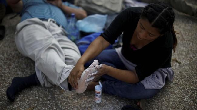 Seorang wanita memijat kaki pasangannya. Keduanya berasal dari El Salvador, dan sedangsinggah untuk beristirahatdi Guatemala. (REUTERS/Jose Cabezas)