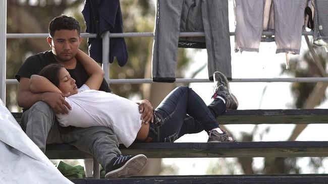 Pasangan lain yang turut menjadi bagian migran besar-besaran dari Amerika Tengah ke Amerika Serikat, menikmati waktu berdua di tengah tempat perlindungan sementara di antara tenda dan pakaian yang baru dicuci. (REUTERS/Lucy Nicholson)
