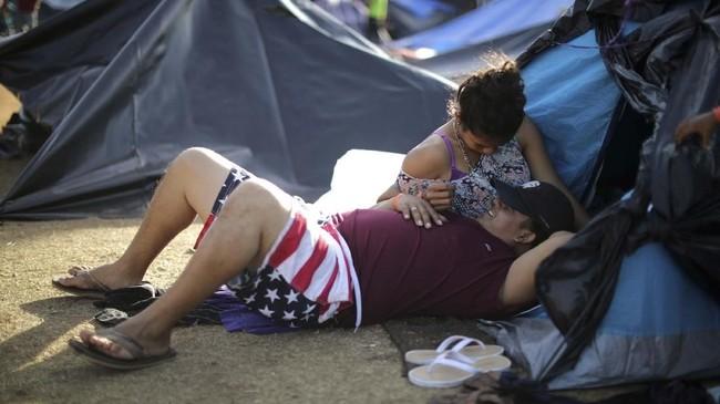 Banyak dari mereka yang merupakan pasangan, seperti Lilian (23) dan Ronny (25) dari Honduras yang sedang beristirahat di tempat perlindungan sementara di Tijuana, Meksiko. (REUTERS/Lucy Nicholson)